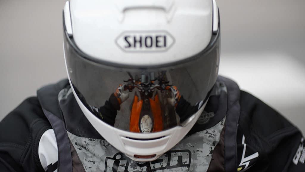 MC-förare i hjälm – i skyddsglaset reflekteras händer som håller i motorcykelstyre